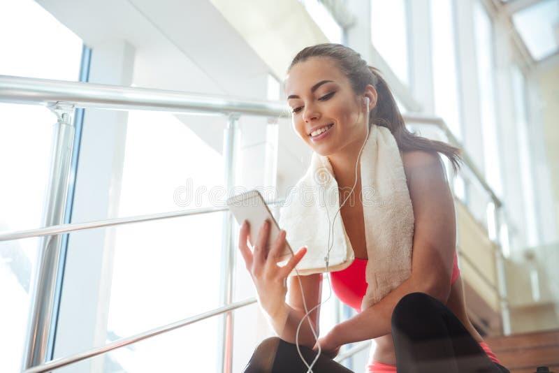 Vrolijke vrouwenzitting in gymnastiek en het luisteren aan muziek stock afbeeldingen
