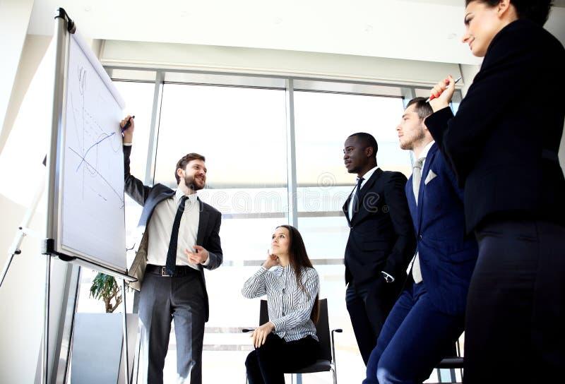Vrolijke zakenman die nieuw bedrijfsproject bespreken met de leden van zijn team stock afbeeldingen