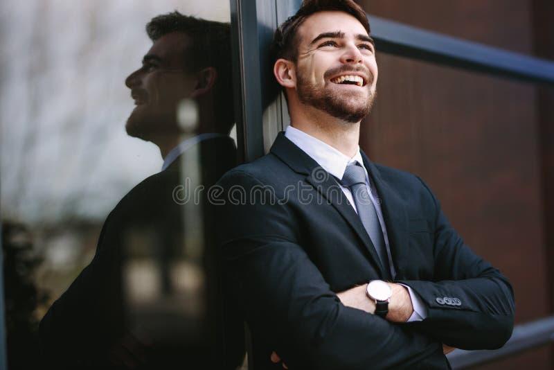 Vrolijke zakenman die zich buiten de bureaubouw bevinden royalty-vrije stock afbeeldingen