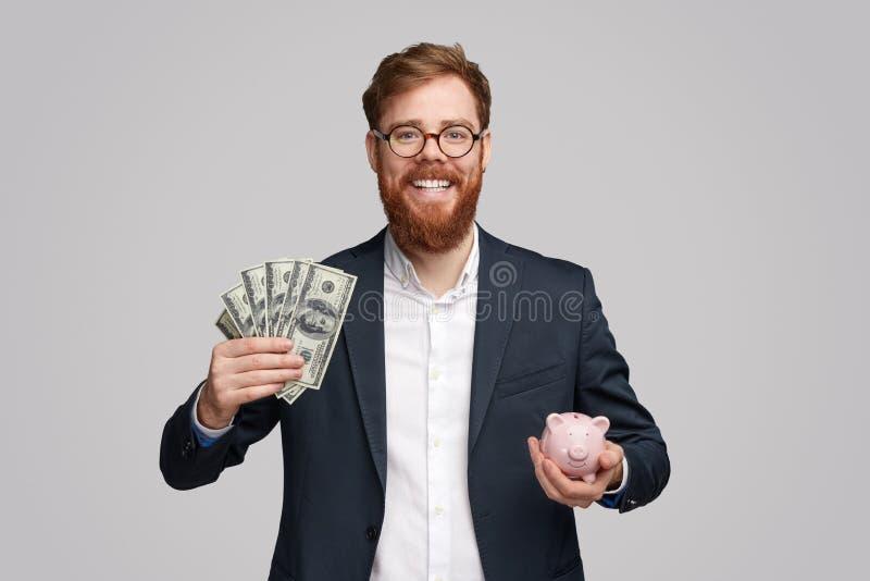 Vrolijke zakenman met contant geld en spaarvarken royalty-vrije stock foto's
