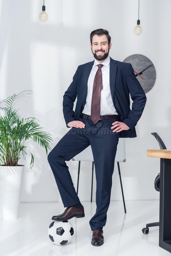 vrolijke zakenman met de handen in de zij status met één been op voetbalbal royalty-vrije stock afbeelding