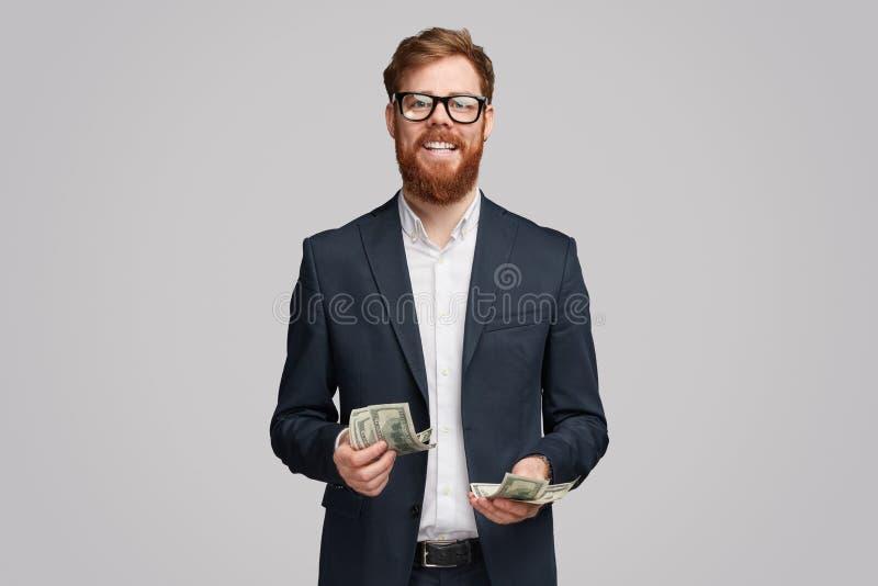 Vrolijke zakenman met stapel van dollars stock fotografie