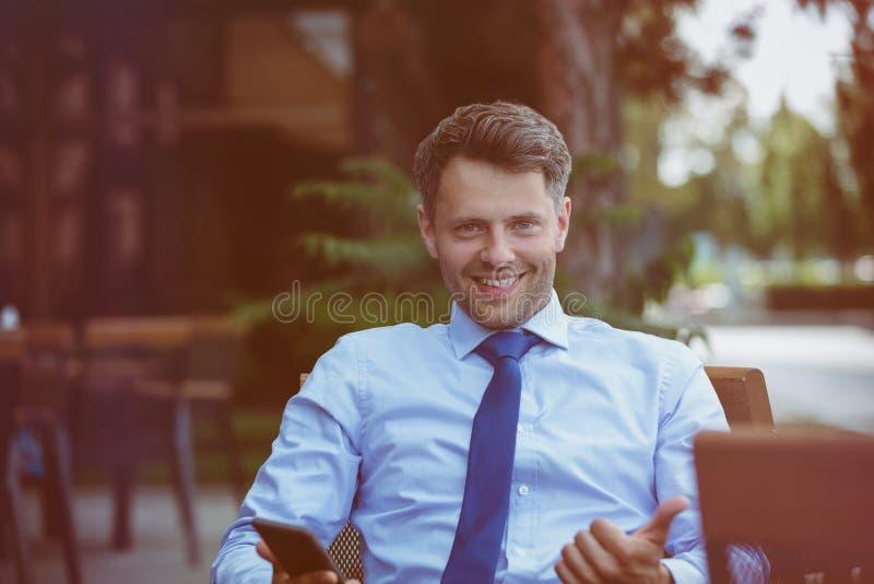 Vrolijke zakenmanzitting op stoel bij stoepkoffie stock fotografie