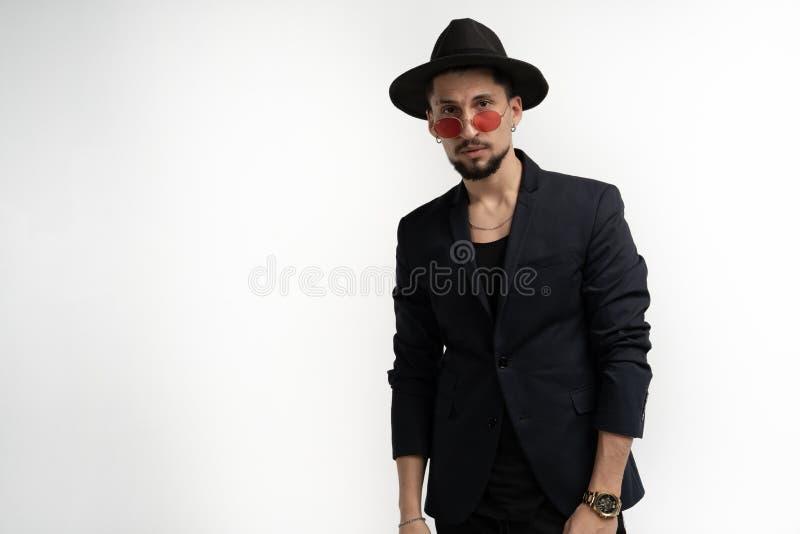 Vrolijke zekere jonge gebaarde mens in zwart kostuum en hoed in rode die zonnebril over witte achtergrond wordt ge?soleerd stock afbeeldingen