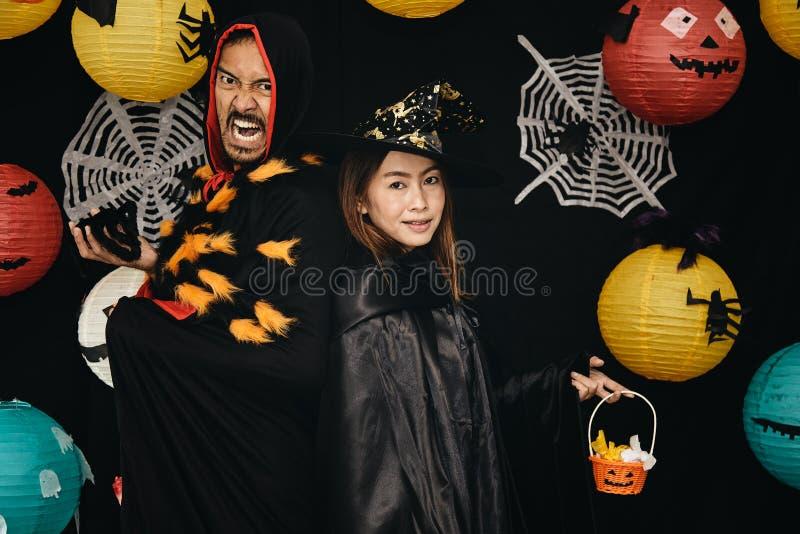 Vrolijke zuster en haar broer die in tovenaar en heksenkostuums Halloween vieren stock foto