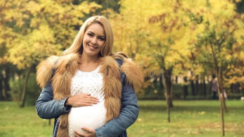 Vrolijke zwangere vrouw die en buik, geboortenregeling, het wachten glimlachen houden op stock afbeelding