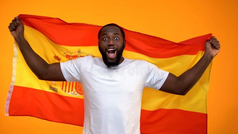 Vrolijke zwarte sportventilator die Spaanse vlag houden toejuichend voor nationale teamoverwinning stock foto's
