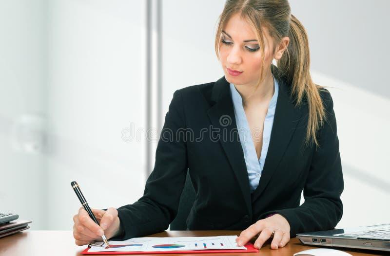 Vrouw aan het werk in haar bureau stock afbeelding