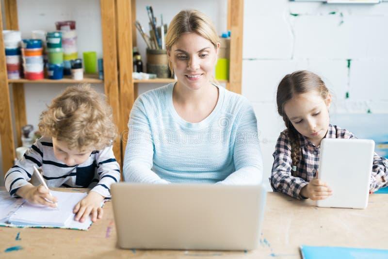 Vrouw aan het werk met kinderen stock foto's