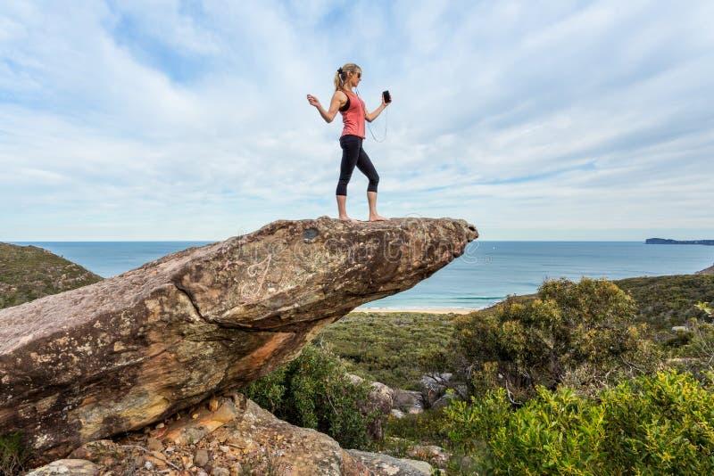 Vrouw aan muziek luisteren of een playlist die hoog omhoog op een in evenwicht brengende rots op bergrand stock foto
