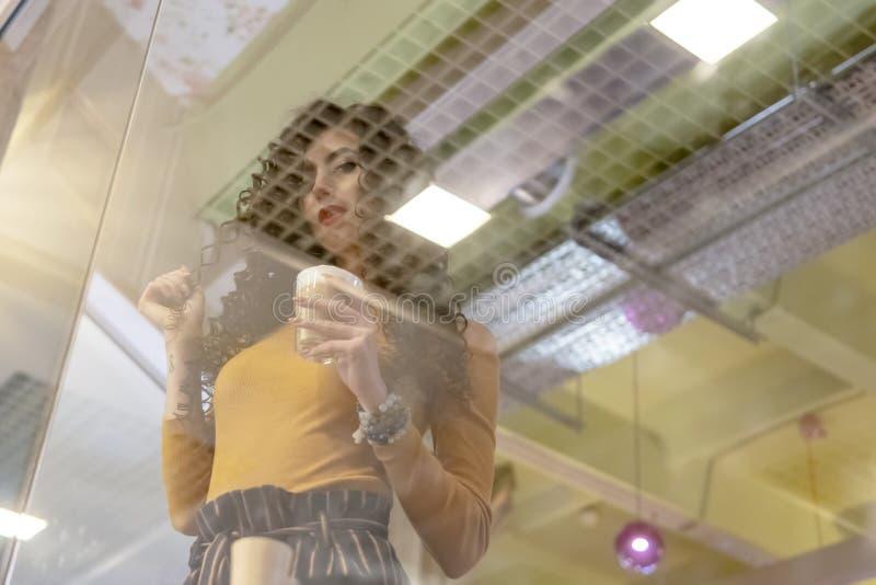 Vrouw achter een glas in koffie royalty-vrije stock afbeelding