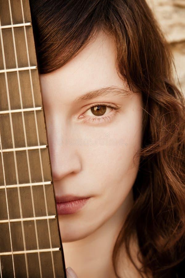 Vrouw achter gitaar fretboard stock afbeelding