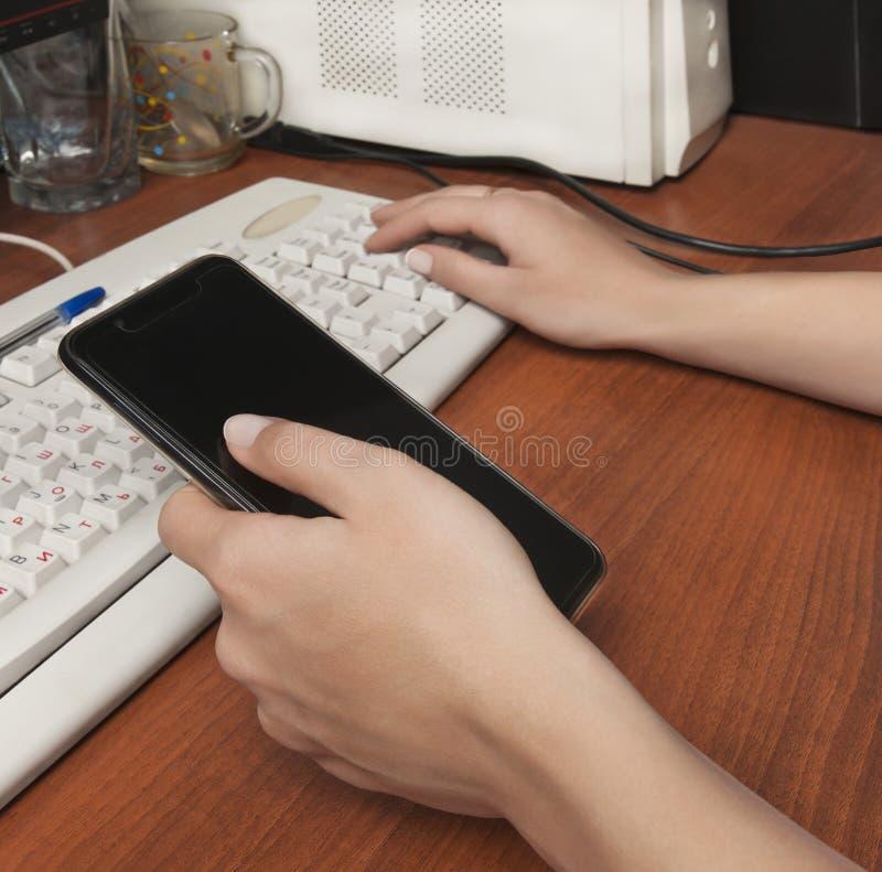 Vrouw achter het toetsenbord, die een celtelefoon houden stock foto's