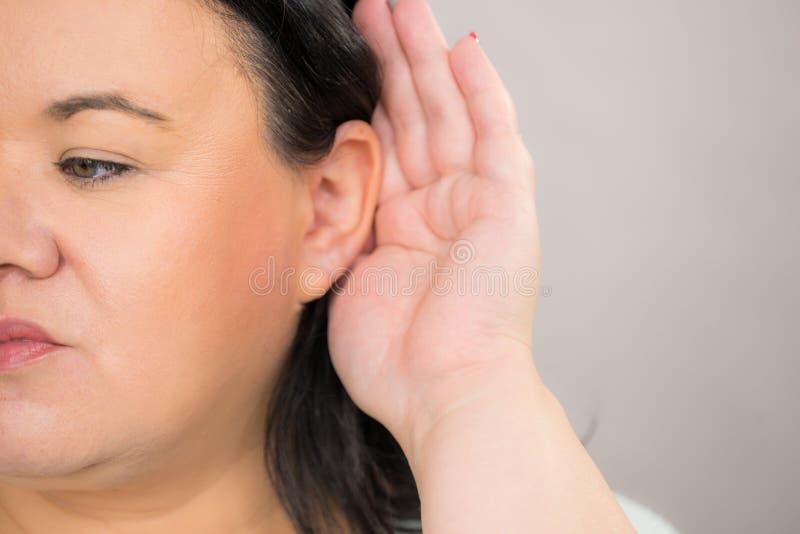 Vrouw afluisteren die aan geruchten luisteren royalty-vrije stock fotografie