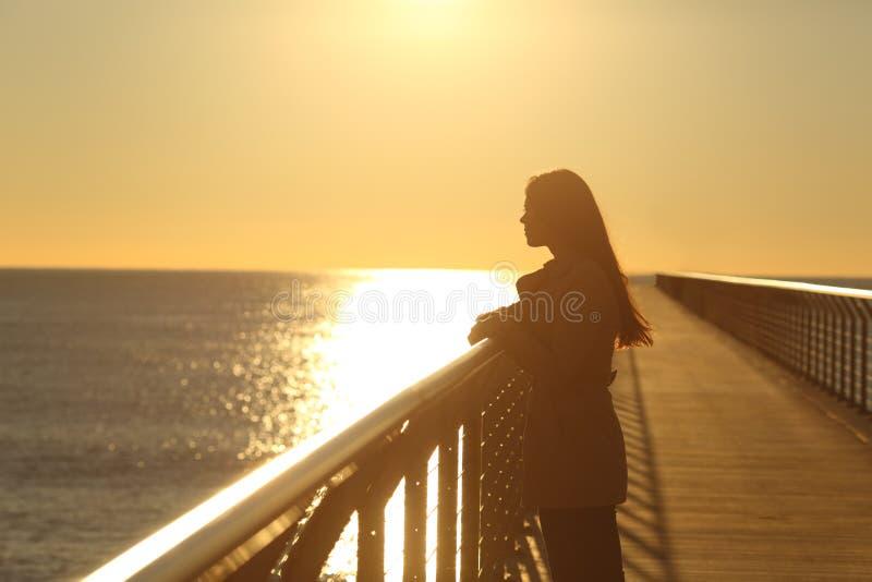 Vrouw alleen het overwegen oceaan bij zonsondergang stock foto