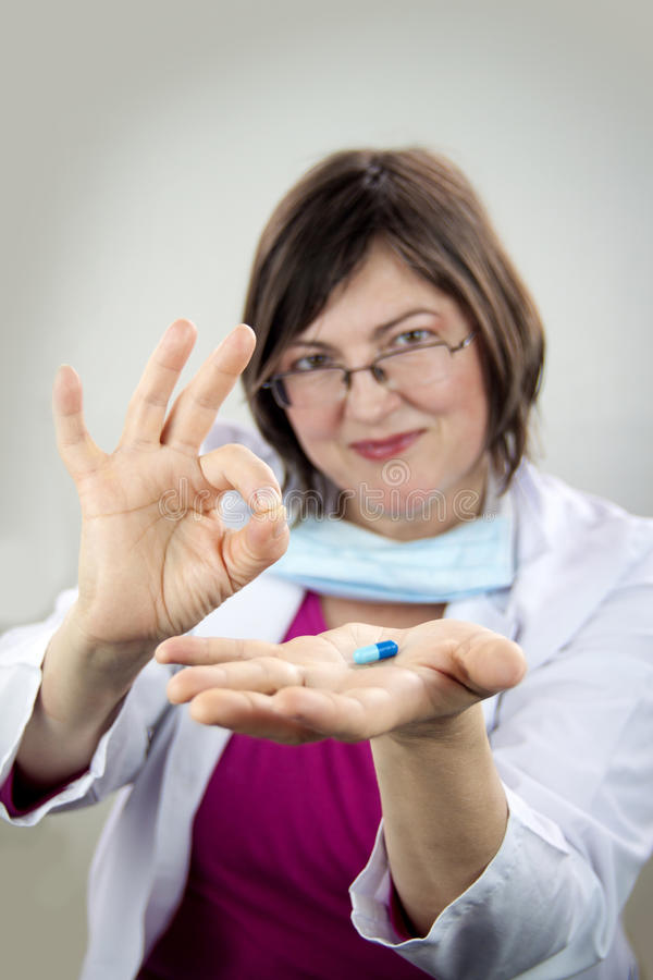Vrouw arts die blauwe pil houden stock foto's