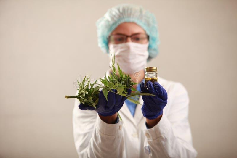 Vrouw arts die een een cannabisblad en olie houden Alternatieve geneeskunde royalty-vrije stock foto's