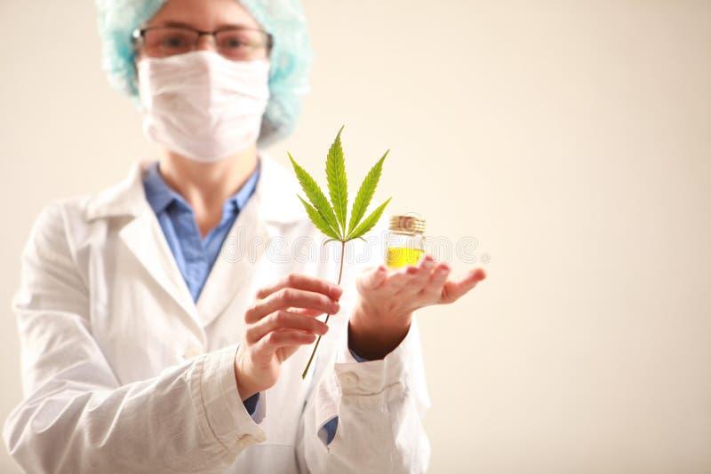 Vrouw arts die een een cannabisblad en olie houden Alternatieve geneeskunde stock foto