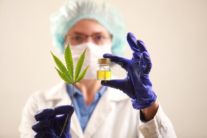 Vrouw arts die een een cannabisblad en olie houden Alternatieve geneeskunde royalty-vrije stock fotografie