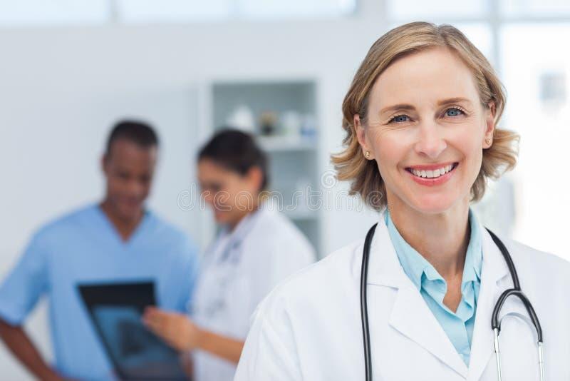 Vrouw arts die en aan de camera glimlachen kijken royalty-vrije stock fotografie