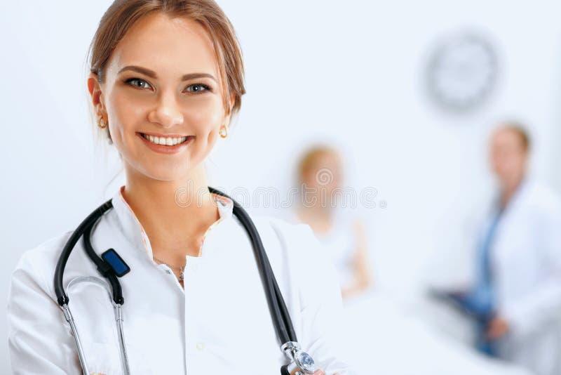 Vrouw arts die en aan de camera glimlachen kijken stock afbeelding