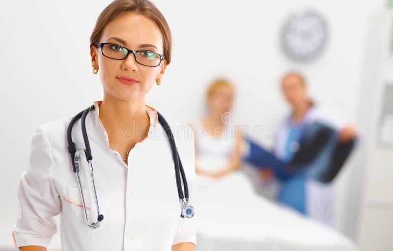 Vrouw arts die en aan de camera glimlachen kijken royalty-vrije stock afbeelding