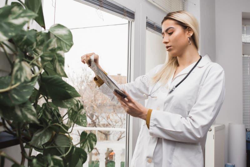 Vrouw arts die filmröntgenstraal controleren stock afbeelding