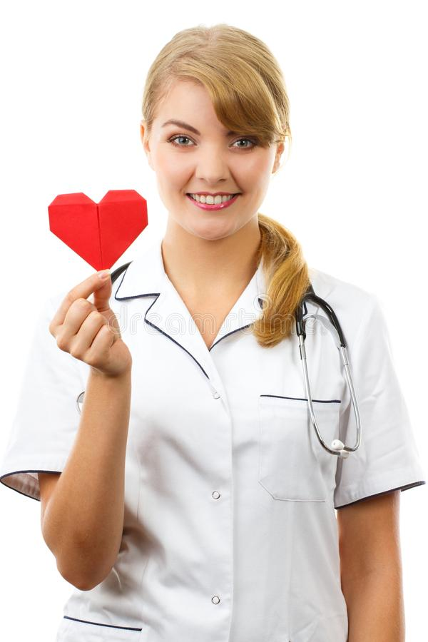 Vrouw arts die met stethoscoop rood hart, gezondheidszorgconcept houden royalty-vrije stock afbeeldingen
