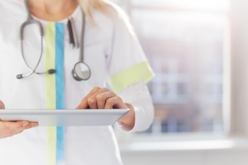 Vrouw arts die tabletcomputer in het ziekenhuis met behulp van royalty-vrije stock afbeeldingen