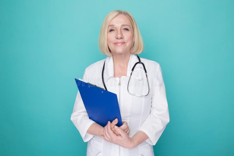 Vrouw arts met geïsoleerde stethoscoop en blauwe tablet status stock foto