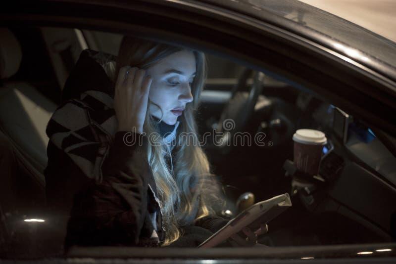 Vrouw in auto met tablet bij nacht stock foto's