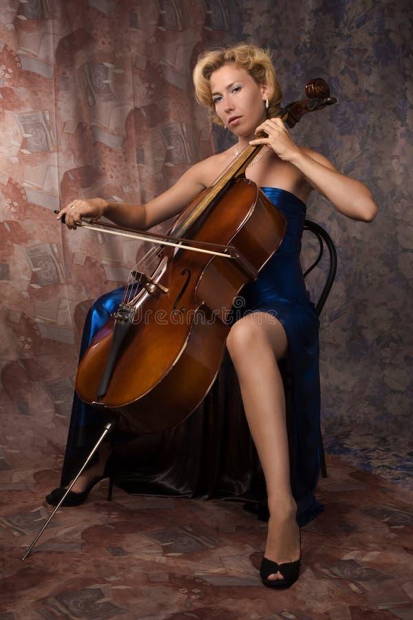 Vrouw in avondjurk het spelen cello stock foto