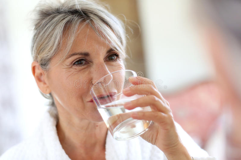 Vrouw in badjas drinkwater royalty-vrije stock afbeelding