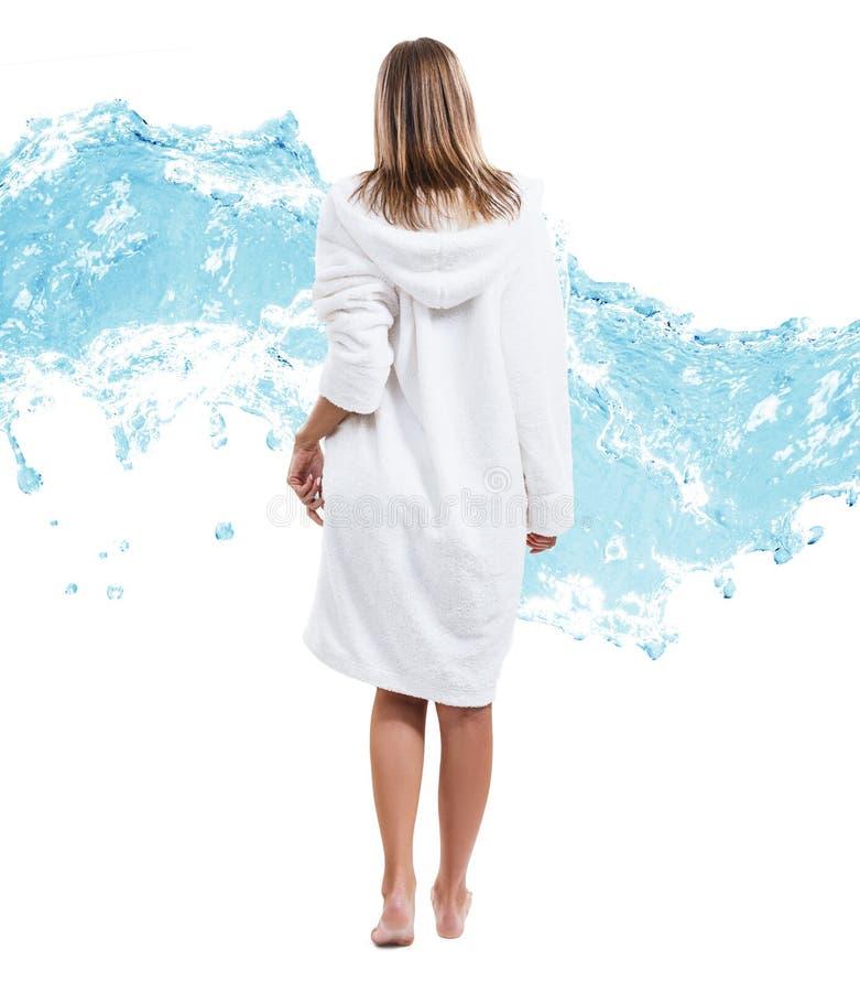 Vrouw in badjas over de achtergrond van de waterplons royalty-vrije stock afbeelding
