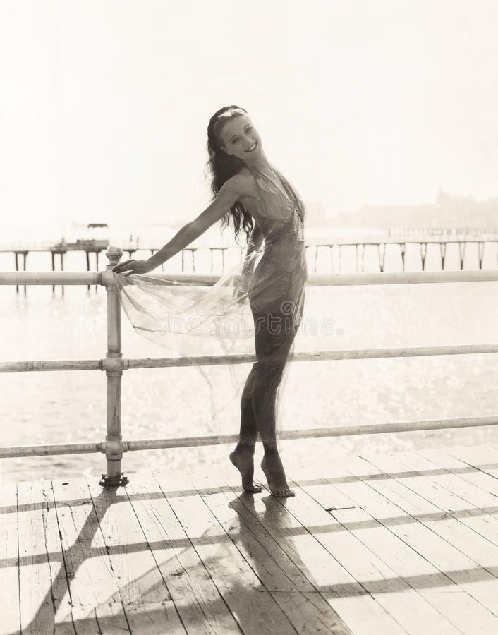Vrouw in badpak bij tiptoe het stellen op pijler stock afbeeldingen
