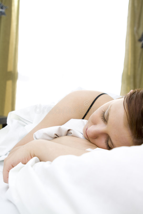 Vrouw in bed stock afbeelding