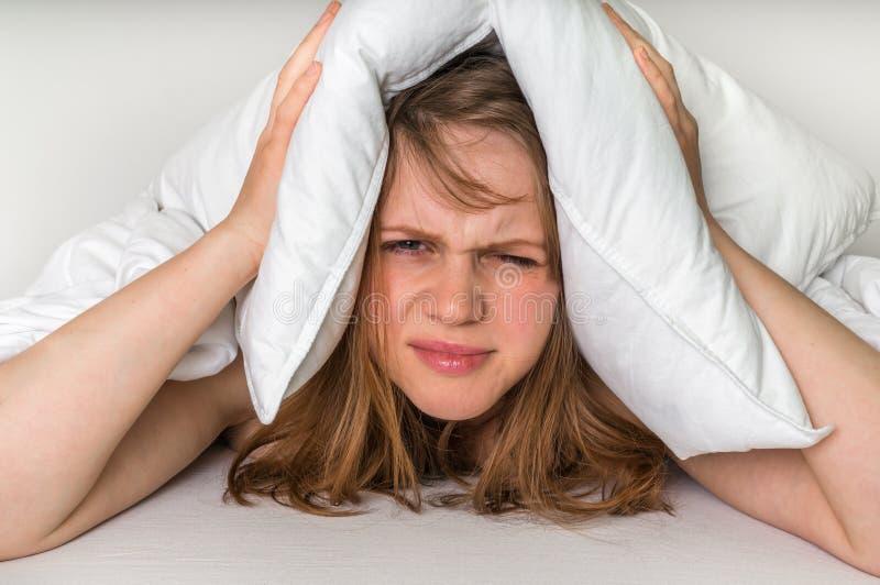 Vrouw in bed die oren behandelen met hoofdkussen wegens lawaai stock afbeelding