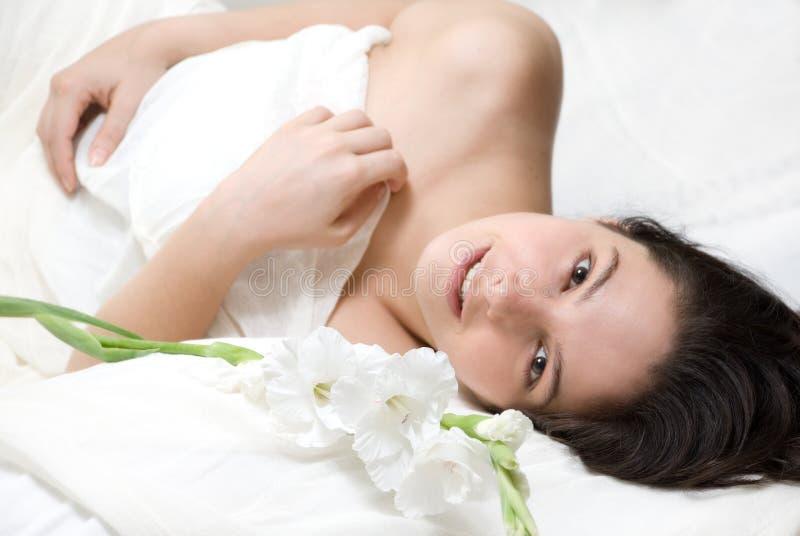 Vrouw in bed en bloemen stock foto
