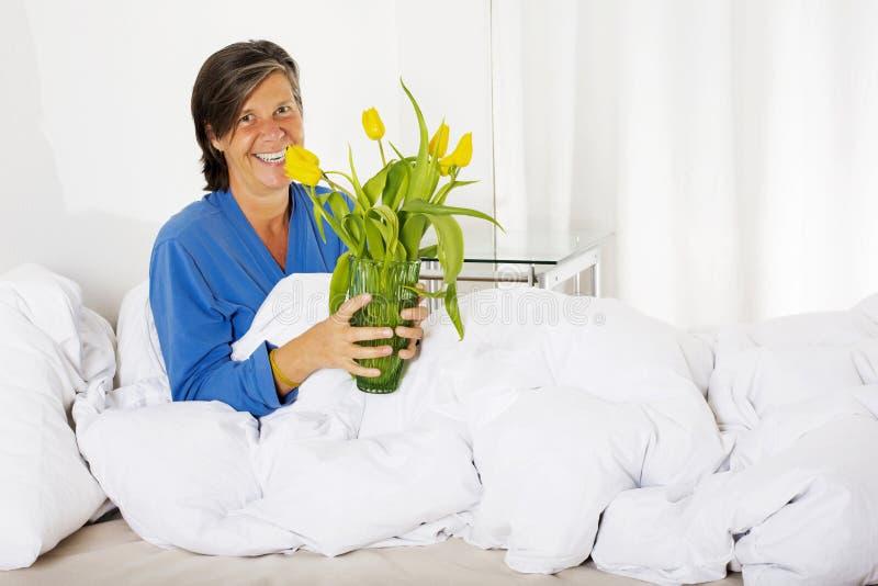 Vrouw in Bed met bloemen royalty-vrije stock afbeeldingen