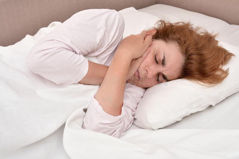 Vrouw in bed met tandpijn die haar wang houden stock fotografie