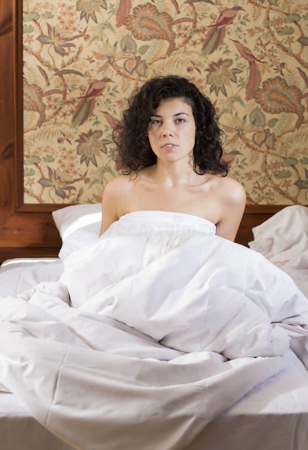 Vrouw in bed na rusteloze nacht wordt gewekt die stock afbeelding