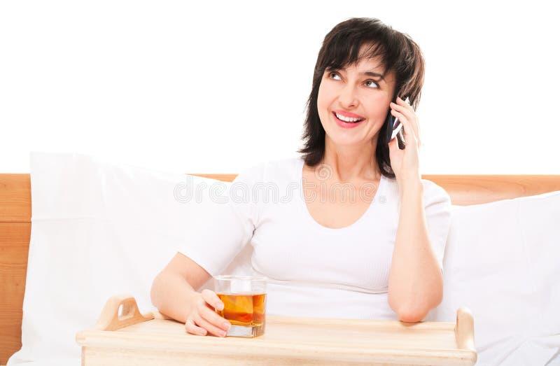 Vrouw in bed talkin telefonisch royalty-vrije stock fotografie