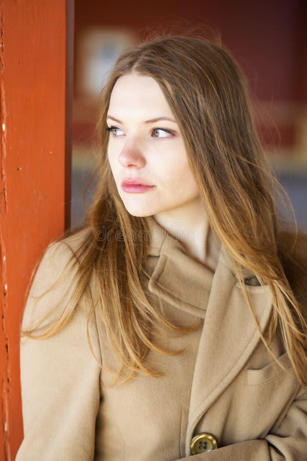 Vrouw in beige laag met droevig gezicht stock foto
