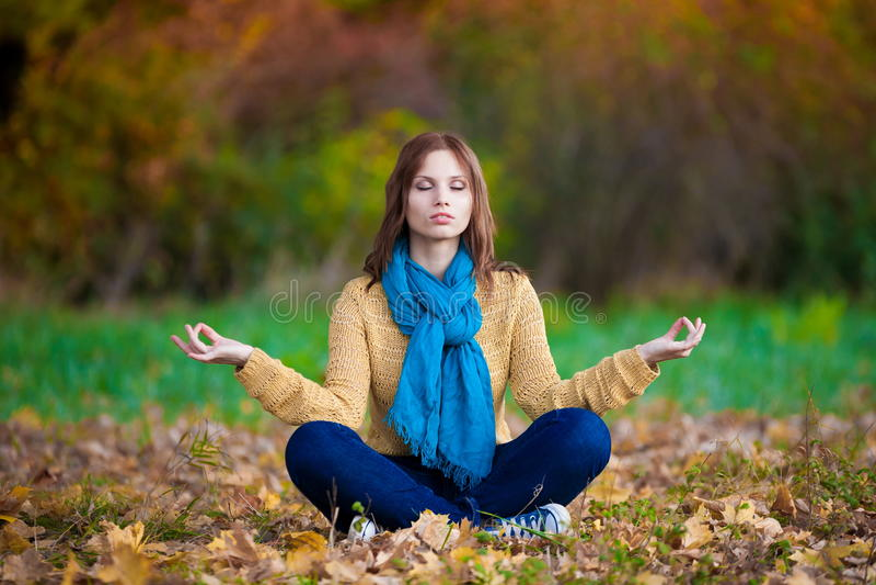 Vrouw in beige sweater, jeans en sjaalmeditatie stock foto