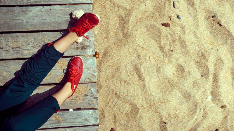 Vrouw benen in rode laarzen op houten pier nabij zandig strand Begrip ontspanning, reis en sereniteit, levensstijl royalty-vrije stock afbeelding