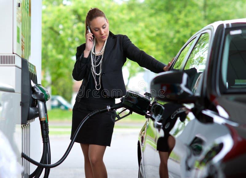 Vrouw in benzinepost stock foto's
