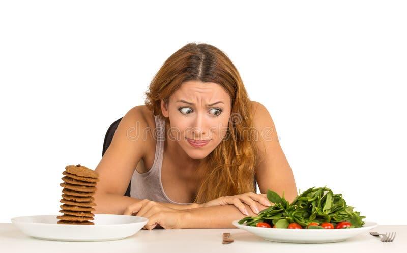 Vrouw besluiten die of om gezond voedsel of zoete koekjes te eten stock foto