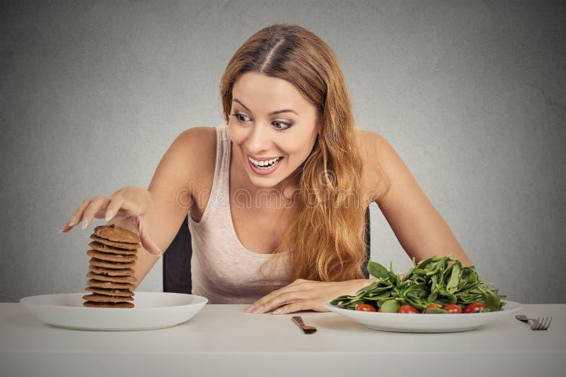 Vrouw besluiten die of om gezond voedsel of zoete koekjes te eten zij die hunkeren naar stock fotografie