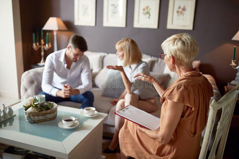 Vrouw in bespreking met echtgenoot bij psycholoog stock afbeelding