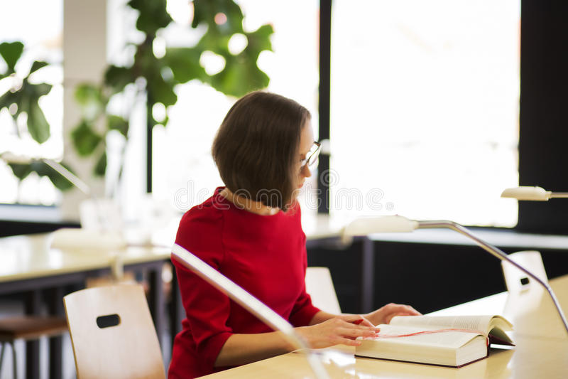 Vrouw in bibliotheek gelezen boek bij dag royalty-vrije stock foto